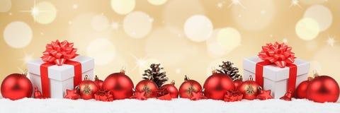 Los regalos de la Navidad presentan a decoración de la bandera de las bolas backgrou de oro Fotografía de archivo