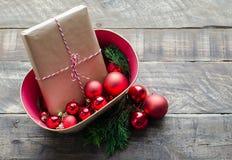 Los regalos de Navidad con el pino ramifican en fondo de madera rústico Imagen de archivo
