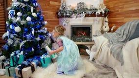 Los regalos debajo del árbol de navidad el mañana de la Nochebuena, la muchacha toman a regalo la sorpresa alegre del ` s del Año almacen de metraje de vídeo