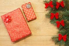 Los regalos del Año Nuevo/la Navidad en el paquete, árbol con rojo arquean en la plantilla de madera del fondo Foto de archivo libre de regalías