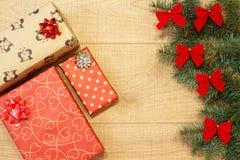 Los regalos del Año Nuevo/la Navidad en el paquete, árbol con rojo arquean en la plantilla de madera del fondo Foto de archivo