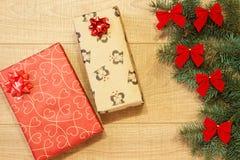 Los regalos del Año Nuevo/la Navidad en el paquete, árbol con rojo arquean en la plantilla de madera del fondo Imágenes de archivo libres de regalías