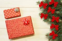 Los regalos del Año Nuevo/la Navidad en el paquete, árbol con rojo arquean en la plantilla de madera del fondo Imagen de archivo