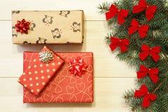 Los regalos del Año Nuevo/la Navidad en el paquete, árbol con rojo arquean en la plantilla de madera del fondo Imagen de archivo libre de regalías