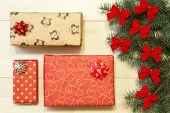 Los regalos del Año Nuevo/la Navidad en el paquete, árbol con rojo arquean en la plantilla de madera del fondo Fotografía de archivo libre de regalías