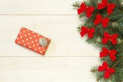 Los regalos del Año Nuevo/la Navidad en el paquete, árbol con rojo arquean en la plantilla de madera del fondo Imagenes de archivo