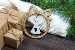 Los regalos envueltos de la Navidad con el ángel blanco en la tabla de madera rústica oscura con los conos y el abeto del pino ra fotografía de archivo