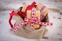 Los regalos envueltos para la Navidad o las tarjetas del día de San Valentín en yute empaquetan Imagen de archivo