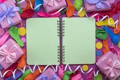 Los regalos festivos del arreglo hinchan la saturación del cuaderno de las flámulas del ultravioleta del fondo fotografía de archivo
