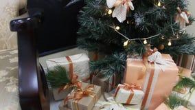 Los regalos presentan las cajas debajo de árbol de abeto adornado de la Navidad con los juguetes y la luz blanca que guiñan la gu metrajes