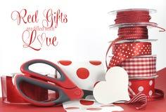 Los regalos rojos se llenan del amor, saludando con el lunar y las cintas, las tijeras, y papel de embalaje llanos Foto de archivo