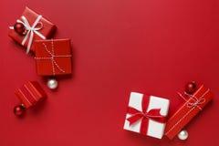 Los regalos simples, modernos de la Navidad roja y blanca presentan en fondo rojo brillante Frontera festiva del día de fiesta fotos de archivo