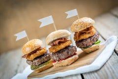 Los resbaladores fortalecen las mini hamburguesas altas que comparten la comida fotos de archivo