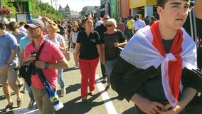 Los residentes de la ciudad y los fanáticos del fútbol están caminando en la zona de la fan almacen de metraje de vídeo