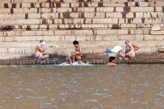 Los residentes locales se lavan en el río Ganges, en el muelle de Varanasi imagenes de archivo