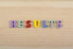 Los RESULTADOS redactan en el fondo de madera compuesto de letras de madera del ABC del bloque colorido del alfabeto, copian el e Foto de archivo libre de regalías