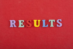 Los RESULTADOS redactan en el fondo rojo compuesto de letras de madera del ABC del bloque colorido del alfabeto, copian el espaci Imagen de archivo libre de regalías