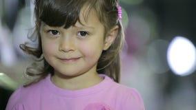 Los retratos de niños en el niño femenino de la tienda que hace expresiones faciales sonríen metrajes