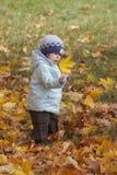 Los retretes del niño con sorpresa en la hoja en otoño parquean Imagen de archivo