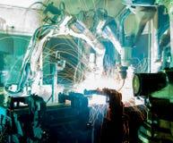 Los robots de soldadura del equipo representan el movimiento Fotos de archivo