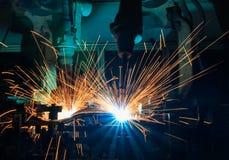 Los robots de soldadura industriales son soldadura del movimiento en cadena de producción Foto de archivo