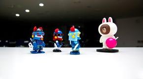 Los robots que llevan dos cascos azules en un fondo blanco están prestando la atención a los monstruos que tienen su lengua roja  Fotografía de archivo libre de regalías