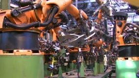 Los robots sueldan con autógena piezas del coche en cadena de producción en la fábrica metrajes