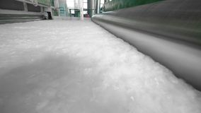 Los rodillos funcionan con una capa de fibra sintética en un transportador de la fábrica almacen de metraje de vídeo