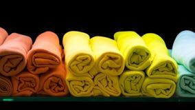 Los rollos amarillos y anaranjados del paño se ponen en el vidrio Fotografía de archivo