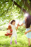 Los rollos de la mamá en un ` s del niño balancean en parque en el verano fotografía de archivo libre de regalías