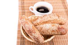 Rollos de pan recientemente cocidos con sésamo con la taza de café Imágenes de archivo libres de regalías