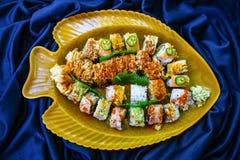 Los rollos de sushi clasificados arreglaron en un disco amarillo de los pescados con el fondo ronzado azul de la tela foto de archivo