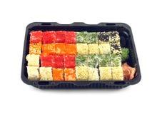 Los rollos de sushi con las huevas Masago de los pescados mienten en el envase de plástico aislado Foto de archivo