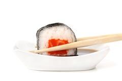 Los rollos de sushi con los salmones, el arroz y el nori en palillos sumergieron en s Fotografía de archivo libre de regalías