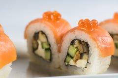 Los rollos de sushi con los salmones, aguacate y queso cremoso, adornados con el caviar rojo, sirvieron en la pizarra blanca Imágenes de archivo libres de regalías