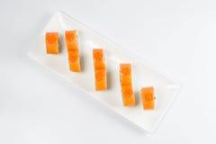 Los rollos de sushi con los salmones, aguacate y queso cremoso, adornados con el caviar rojo, sirvieron en la pizarra blanca Imagenes de archivo