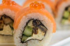 Los rollos de sushi con los salmones, aguacate y queso cremoso, adornados con el caviar rojo, sirvieron en la pizarra blanca Fotografía de archivo