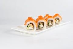 Los rollos de sushi con los salmones, aguacate y queso cremoso, adornados con el caviar rojo, sirvieron en la pizarra blanca Imagen de archivo libre de regalías