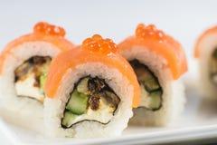 Los rollos de sushi con los salmones, aguacate y queso cremoso, adornados con el caviar rojo, sirvieron en la pizarra blanca Foto de archivo libre de regalías