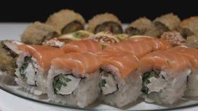 Los rollos de sushi en una cámara de la vista lateral de la placa mueven de izquierda a derecha a cámara lenta almacen de video