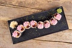 Los rollos de sushi servidos con adornan, visión superior Foto de archivo