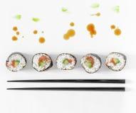 Los rollos de sushi y los palillos con salpican de movimientos de la salsa y del cepillo de soja del wasabi Imágenes de archivo libres de regalías