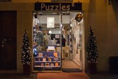 Los rompecabezas almacenan con las decoraciones de la luz de la Navidad de la tarde Imagenes de archivo