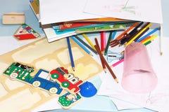 Los rompecabezas de madera, los lápices coloreados y los libros se dispersan en la tabla del ` s de los niños fotografía de archivo libre de regalías