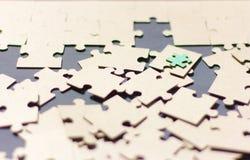 Los rompecabezas dispersaron en los rompecabezas de la tabla, el principio de la asamblea Imagen de archivo
