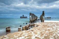 Los rompeolas de madera congelados alinean a la plataforma del torpedo de la Segunda Guerra Mundial en el mar Báltico Fotografía de archivo