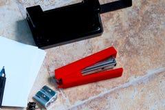 Los sacapuntas, el sacador de agujero, la grapadora, el papel de nota y la pluma mienten en la superficie imágenes de archivo libres de regalías