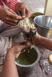 Los sacerdotes hindúes preparan la leche de la marijuana en los ghats del río de Yamuna foto de archivo