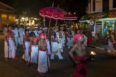 Los sacerdotes y la comitiva del templo caminan a lo largo de una calle en Kandy en la realización del Esala Perahera en Kandy, S fotos de archivo