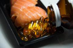 Los salmones del sushi sirvieron con las píldoras del aceite de pescado vertidas del aislador de la botella Fotografía de archivo